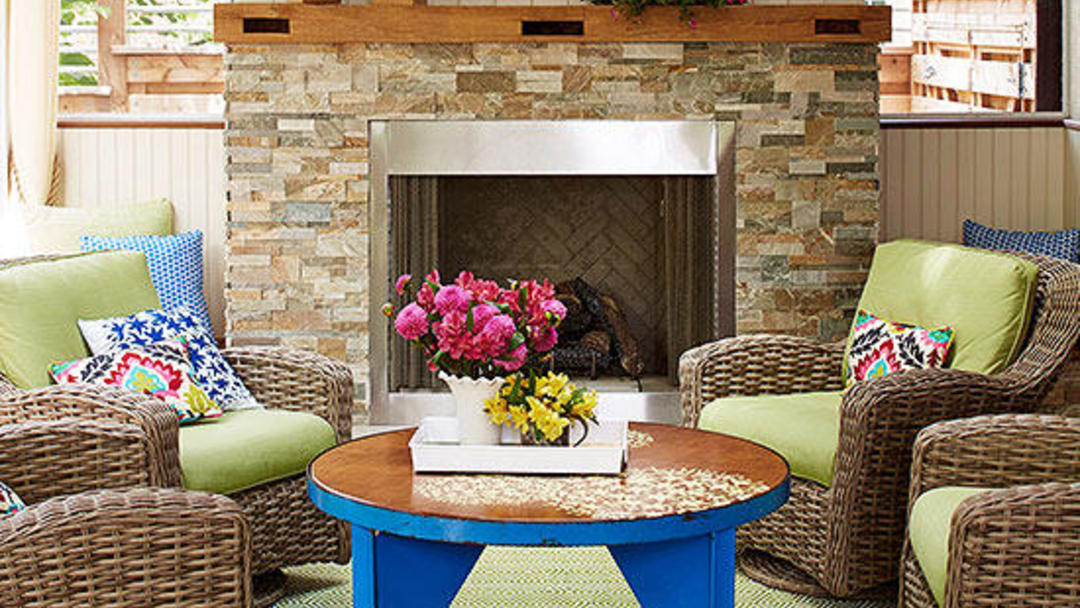 Fireplace with table in front of it and four wicker chairs