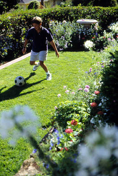 Boy Playing Soccer in Yard