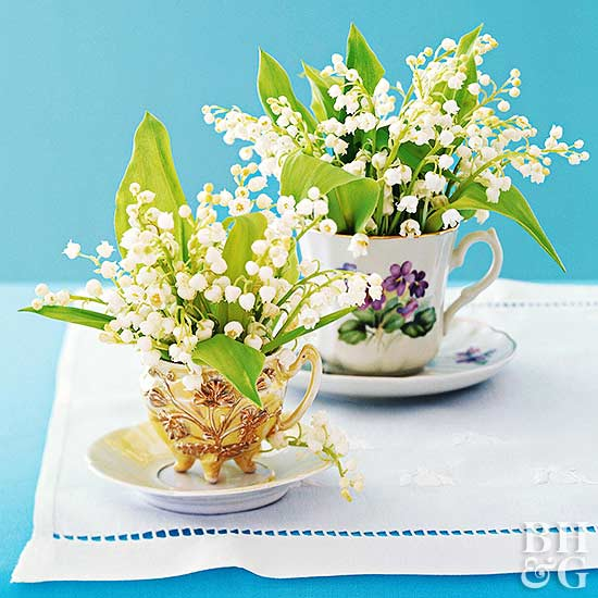 vintage cups and saucers filled with lily of the valley