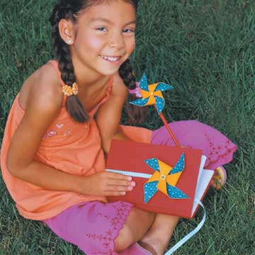 girl with pinwheel journal and pencil