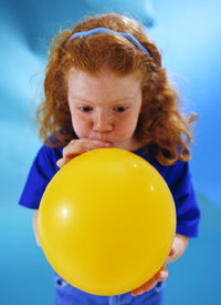 child blowing up balloon