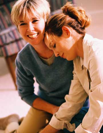 Mother and adolescent daughter sitting on floor