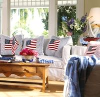 White couch with 3 white pillows with American flags stitched on pillows