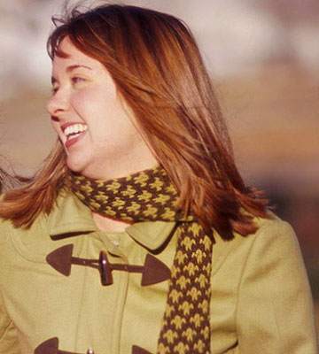 Close up of woman wearing a brown patterned knitted scarf