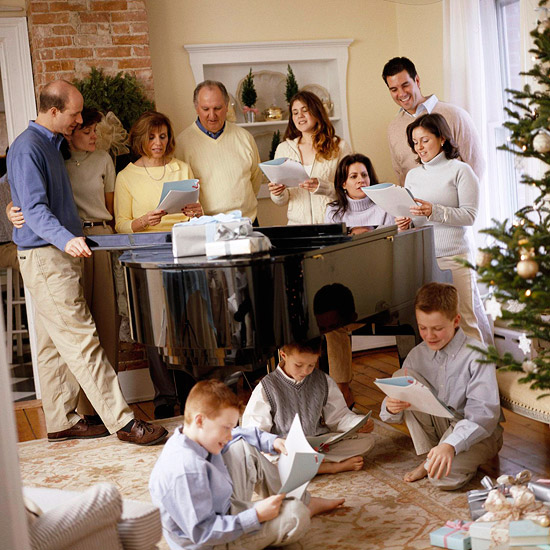 everybody around piano by Christmas trees