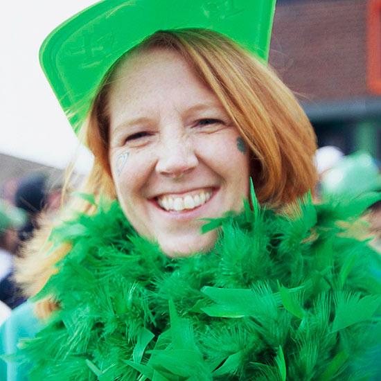 Female spectator wearing a green hat and green boa at the Chicago South Side Irish Parade in the Beverly, Illinois Neighborhood