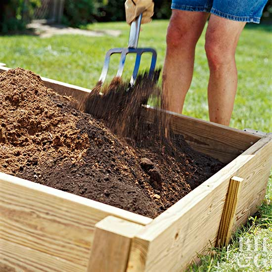 adding soil to raised garden bed