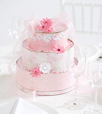 Pink wedding cake centerpiece made from tins, patterned paper, gems, and flowers