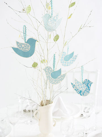 Nature-inspired wedding centerpiece made from painted tree branches and patterned-paper birds