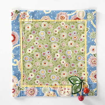 Green, yellow, red, blue floral patterned table mat embellished with wooden cherries