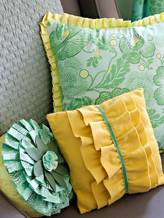 Green and yellow pillows with ruffles and pleats.