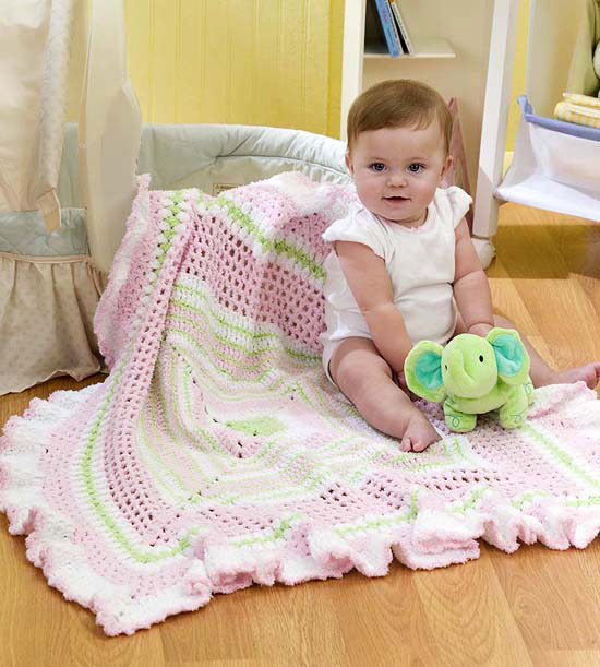 Baby sitting on crocheted baby blanket