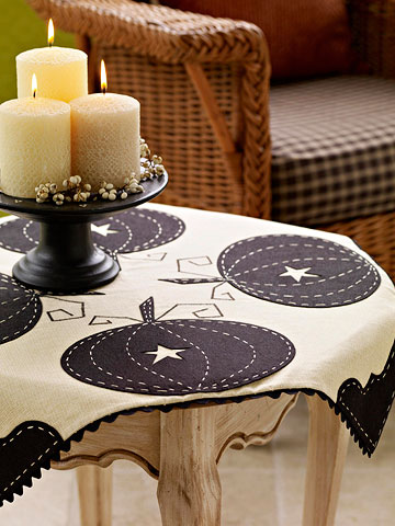 Black pumpkin silhouettes on a creamy white tablecloth