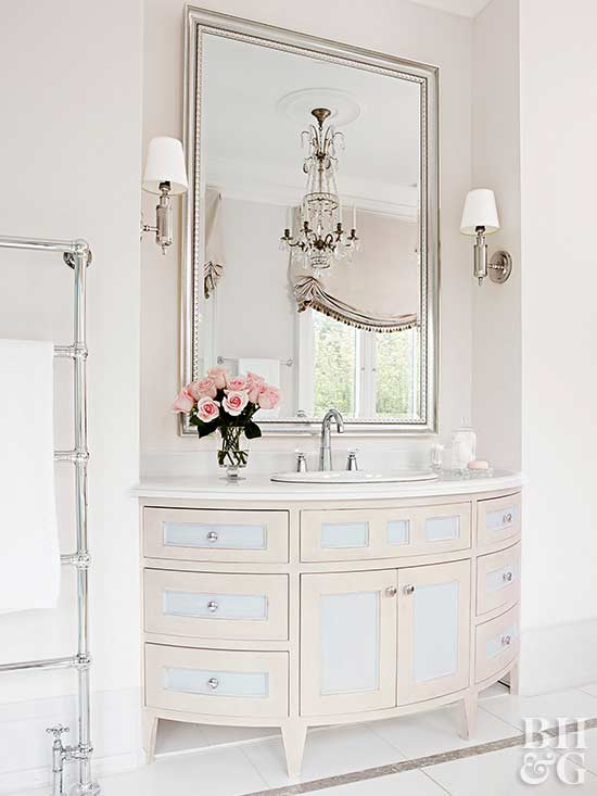 large white bathroom vanity with one sink and large chrome mirror above