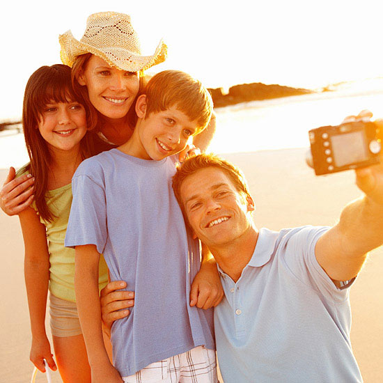 Family taking self portrait with digital camera at sea shore