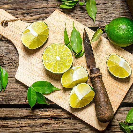 Sliced limes on a board with knife