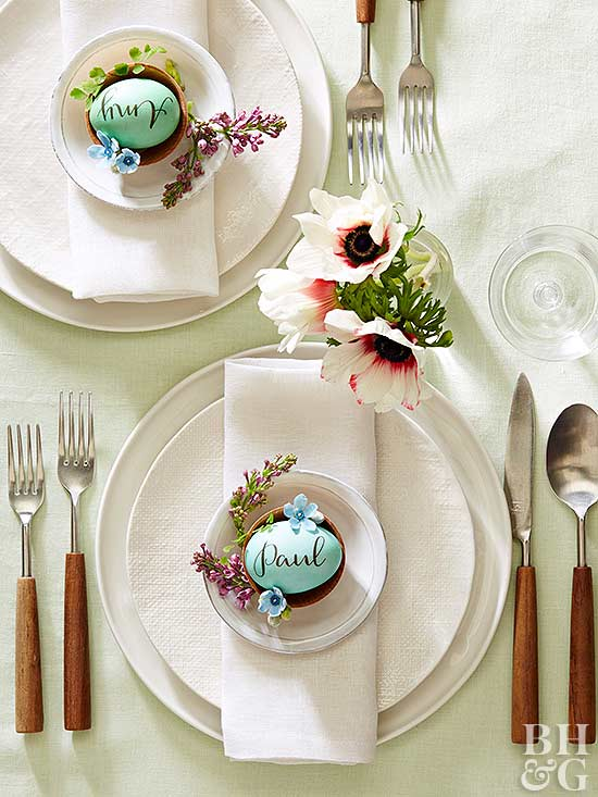 table setting with pretty spring flowers and blue easter eggs in center of plate