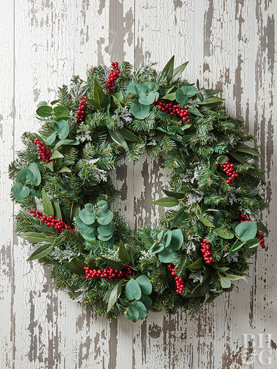 Red berry accented wreath on rustic wood