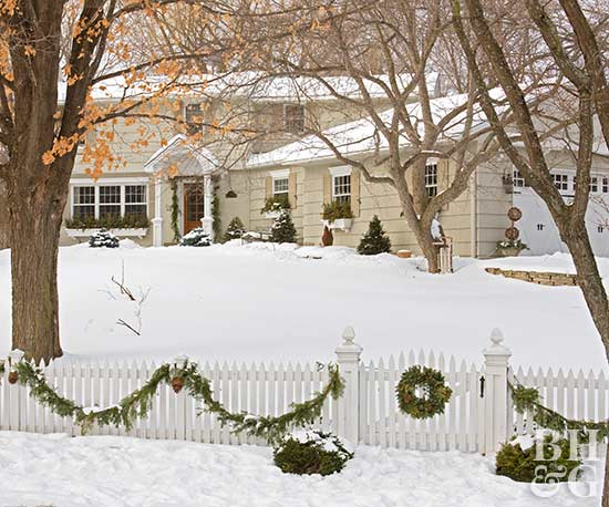 house in winter with white picket fence