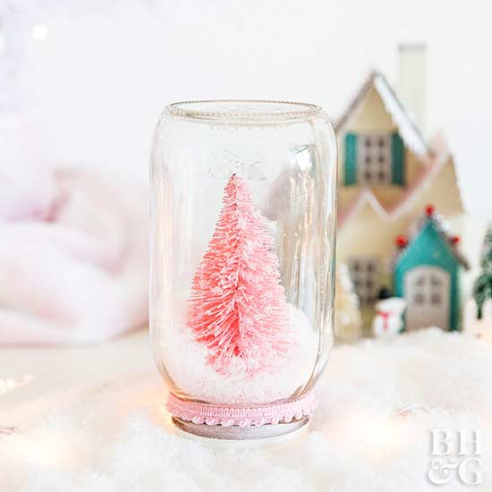 snow globe in front of mini Christmas village