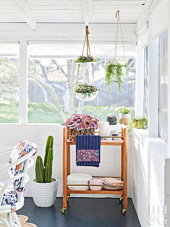 sun room with wooden cart and hanging indoor plants