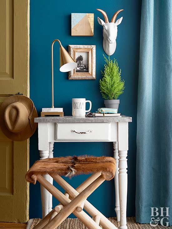 small desk with cow hide covered bench and wall art hanging above