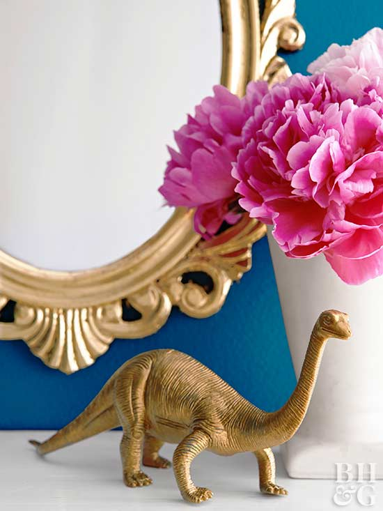 gold dinosaur on shelf with pink flowers in vase and gold mirror in background