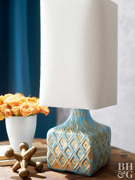 blue and gold lamp with large golden dice on table