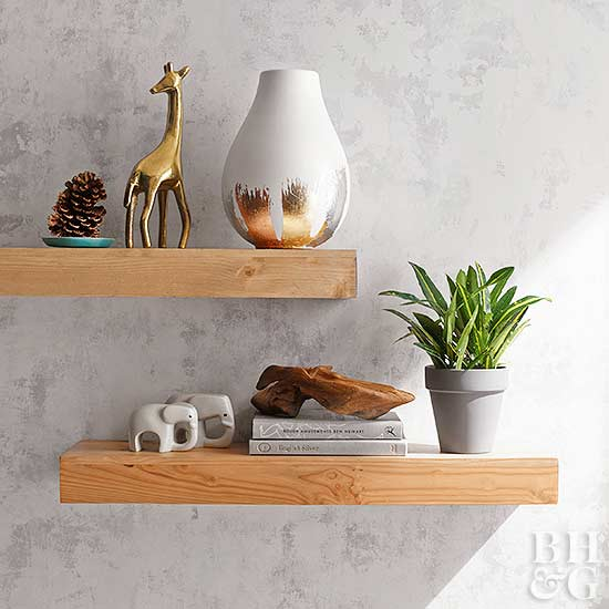 floating wood shelf with knickknacks including books, gold giraffe vase, pine cone and houseplant