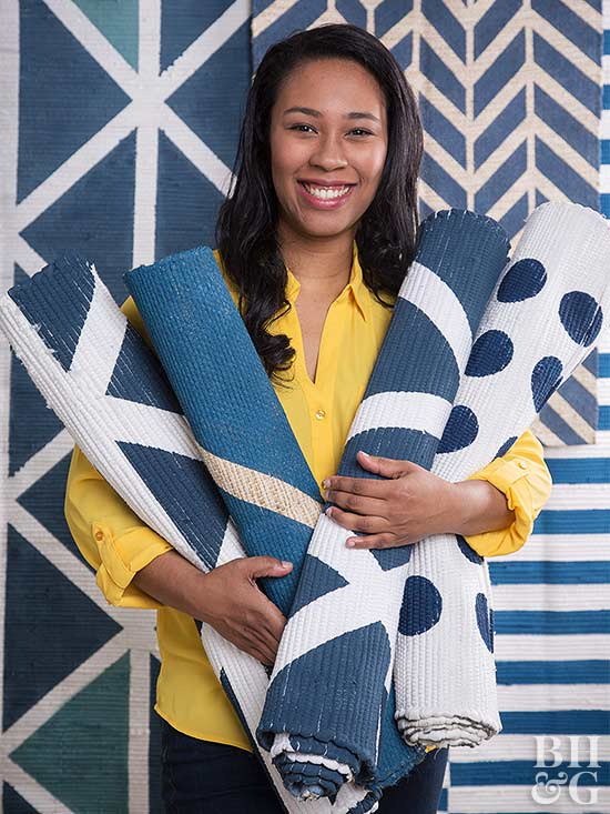 woman holding blue and white rugs