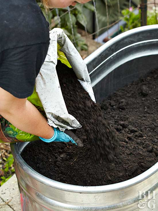 pouring soil into container garden