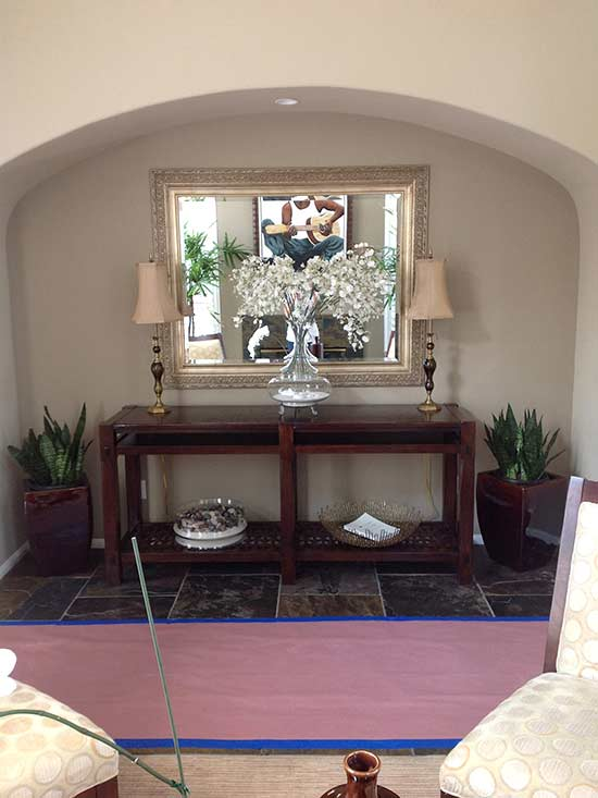archway with table and mirror before