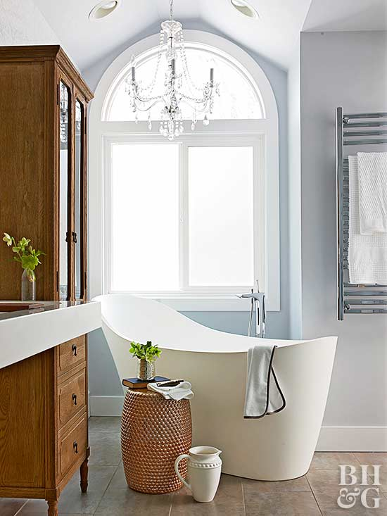 modern white tub with chandelier above