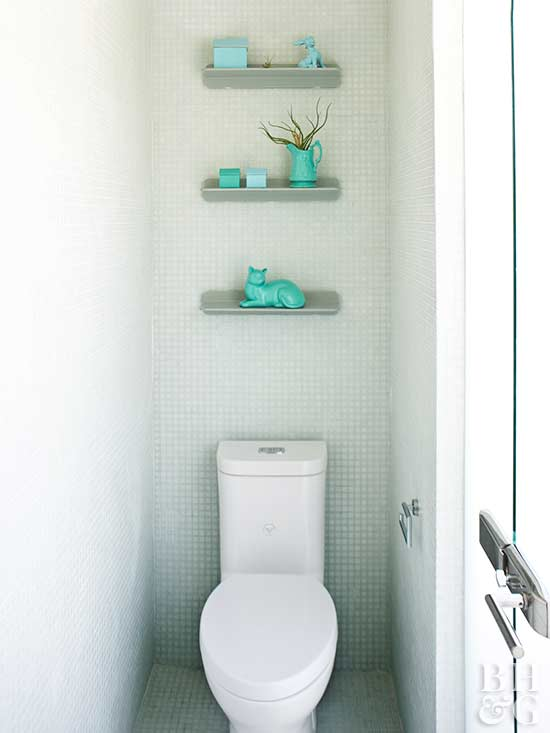 modern toilet with shelf above holding turquoise knick knacks