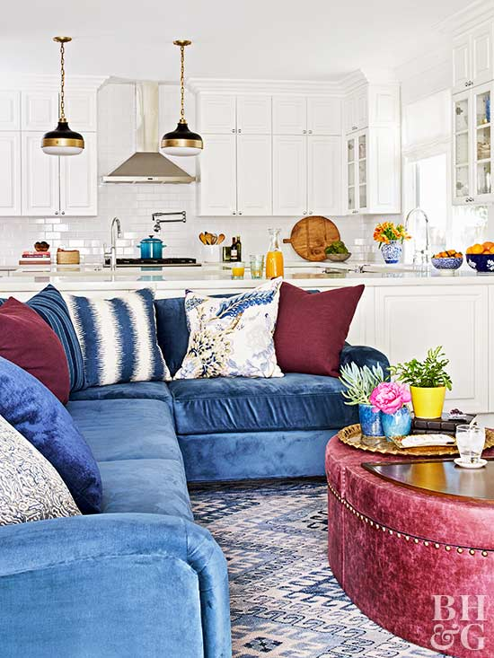 blue velvet couch, red coffee table, white kitchen