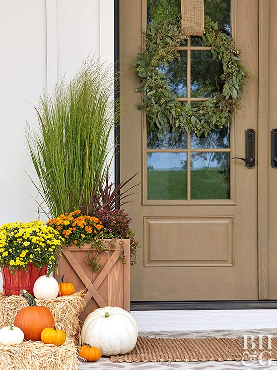 fall front door with wreaths, pumpkins, hay barrel