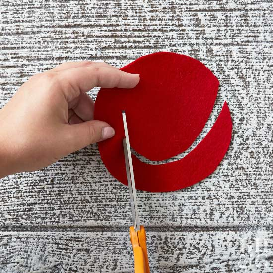 cutting red felt with scissors