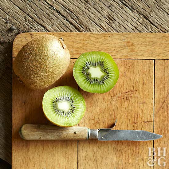 kiwi on wooden cutting board with knife