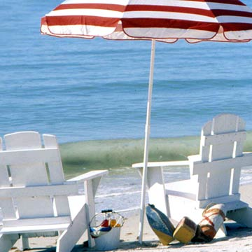 White Lounge Chairs With Red and White Striped Umbrella