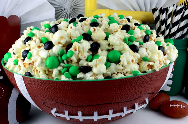 green and black candy popcorn in football bowl