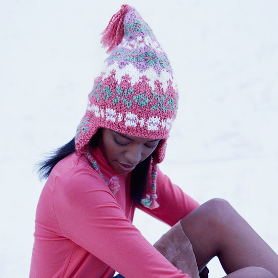 Girl In Pink With Knitted Stocking Sitting In Snow