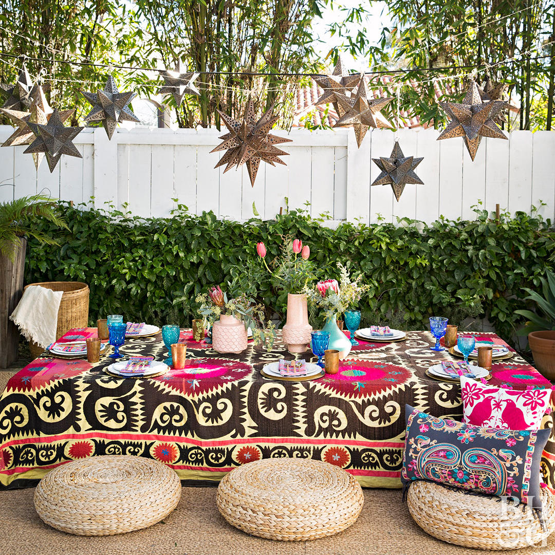 low table and surrounding it with cushions and colorful tablecloth