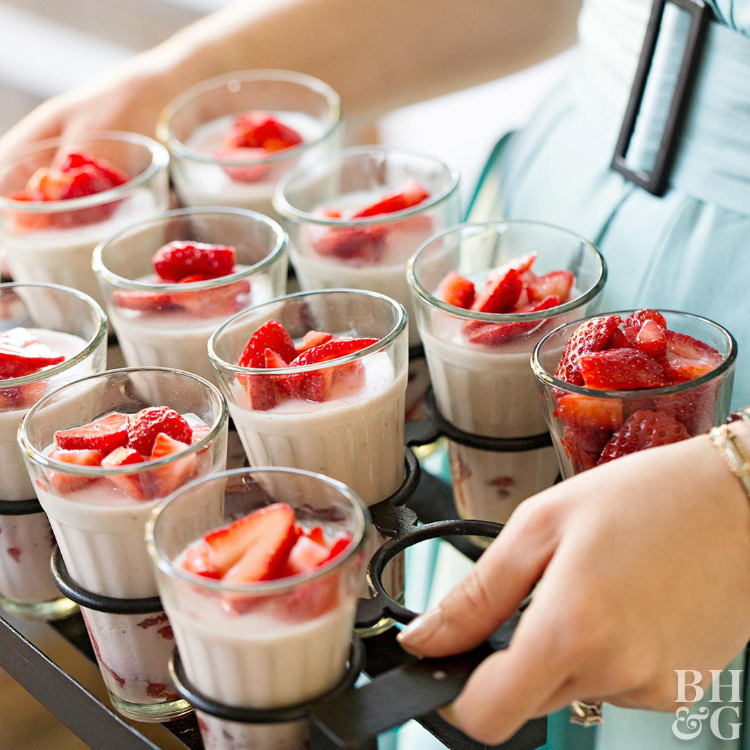 woman holding tray of strawberry parfaits