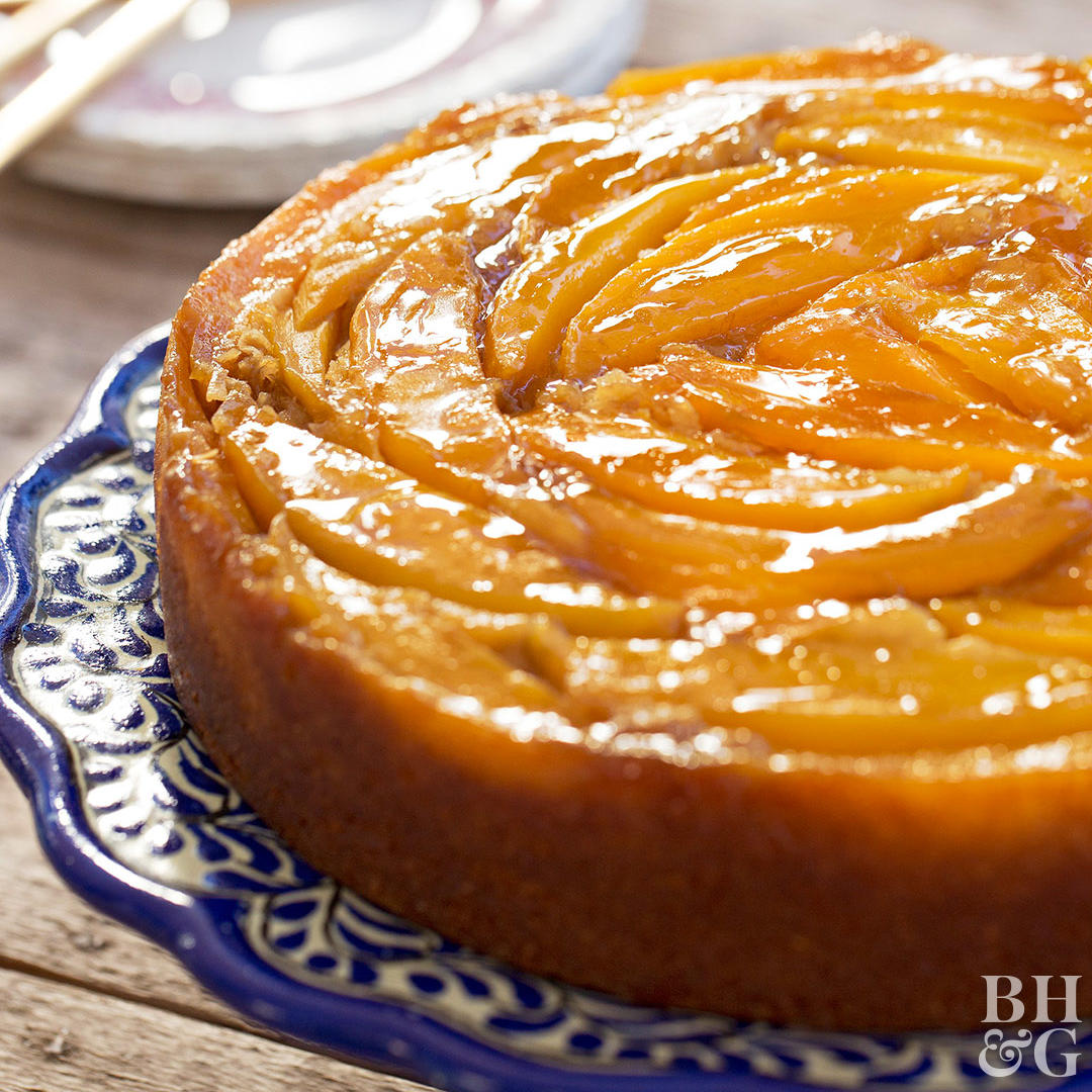 upside down mango cake on blue and white cake stand